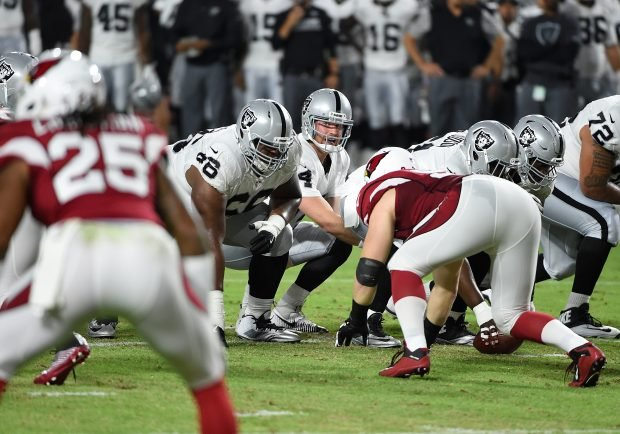 Derek Carr #4 of the Oakland Raiders looks over the defense while calling a play from the line of scrimmage against the Arizona Cardinals at University of Phoenix Stadium on August 12, 2016 in Glendale, Arizona. Raiders won 31-10. (Photo by Norm Hall/Getty Images)