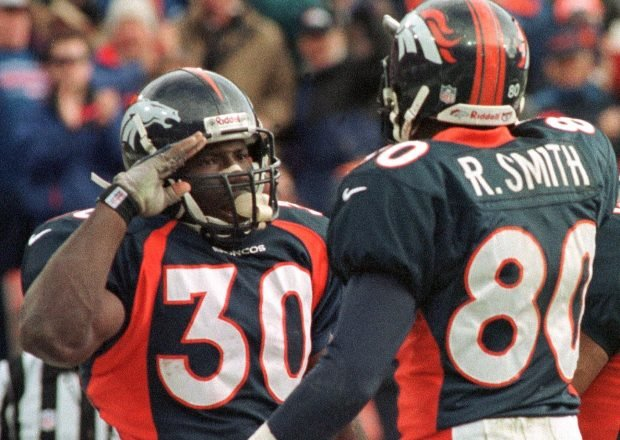 Denver Broncos player Terrell Davis (30) gives the Broncos salute to teammate Rod Smith after Davis scored his first touchdown in the first quarter of their AFC Wild Card playoff game with the Jacksonville Jaguars on Dec. 27 at Mile High Stadium in Denver. Davis went into the Broncos Ring of Fame in 2007 while Smith was inducted in 2012. (Photo by Doug Collier/AFP/Getty Images)