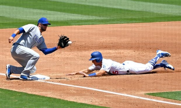 Austin Barnes #15 of the Los Angeles Dodgers beats the throw to David Bote #13 of the Chicago Cubs for a stolen base in the third inning of the game at Dodger Stadium on June 28, 2018 in Los Angeles, California. (Photo by Jayne Kamin-Oncea/Getty Images)