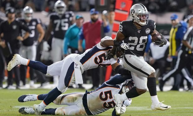 Josh Jacobs #28 of the Oakland Raiders breaks the tackle of Corey Nelson #56 and Bradley Chubb #55 of the Denver Broncos during the fourth quarter of an NFL football game at RingCentral Coliseum on September 9, 2019 in Oakland, California. (Photo by Thearon W. Henderson/Getty Images)