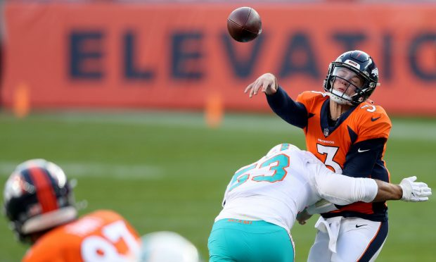 DENVER, COLORADO - NOVEMBER 22: Drew Lock #3 of the Denver Broncos is hit by Kyle Van Noy #53 of the Miami Dolphins as he throws during the second quarter at Empower Field At Mile High on November 22, 2020 in Denver, Colorado. (Photo by Matthew Stockman/Getty Images)